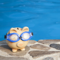 piggy bank wearing goggles sitting next to pool