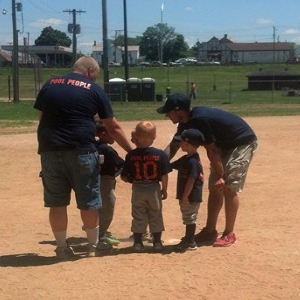 kids and coaches at baseball mound