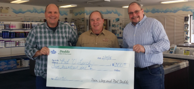 3 men smiling and holding check