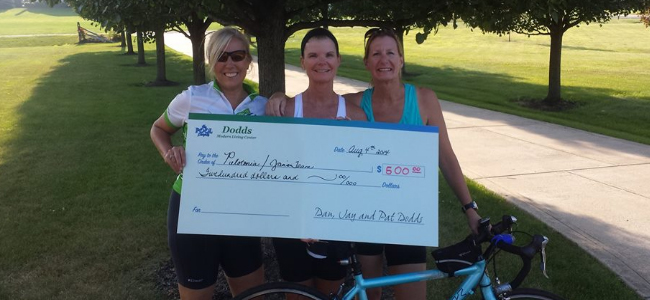 3 ladies smiling and holding check